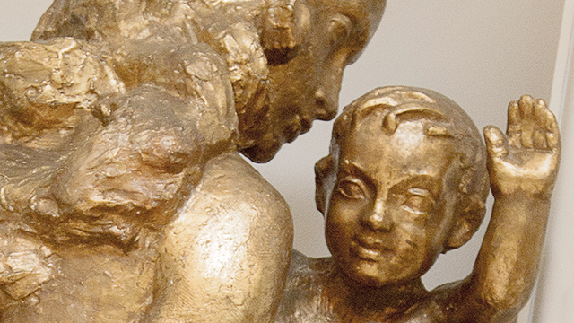 A gilded statue of a child waving their hand